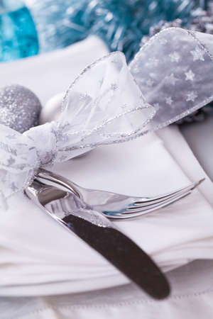 Stylish blue and silver Christmas table setting with a pretty translucent bow on white dinnerware with silver cutlery, pine cones and baubles, high angle close up view photo