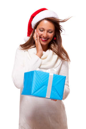 vivacious: Beautiful vivacious woman wearing a red Santa hat laughing and holding up a gift-wrapped blue Christmas gift as she celebrates the festive season, on white
