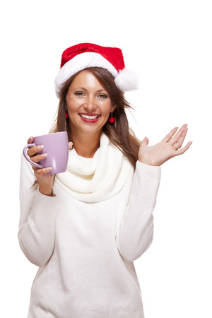 cradling: Cold attractive young woman with a cute smile in a festive red Santa hat sipping a hot mug of coffee that she is cradling in her hands to warm up in the winter weather, on white