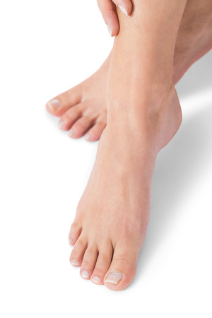 Frau mit ordentlich gepflegten Naturnägeln ohne Lack zeigt ihre Hände und nackten Füßen in einem Beauty-Konzept auf einem weißen Hintergrund