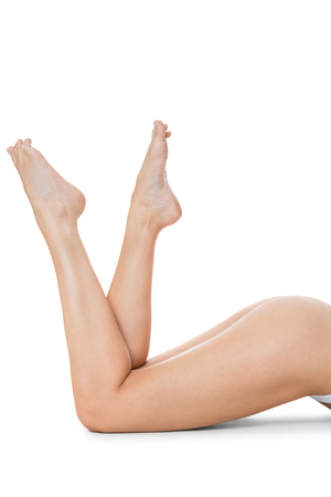 Elegant crossed long bare shapely female legs with bare feet viewed from above isolated on white with copyspace