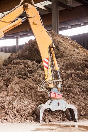 undercover: Escavatore pesante facendo movimento terra parcheggiata sotto copertura in un magazzino aperto di fronte a un enorme mucchio di terra marrone per la costruzione Archivio Fotografico