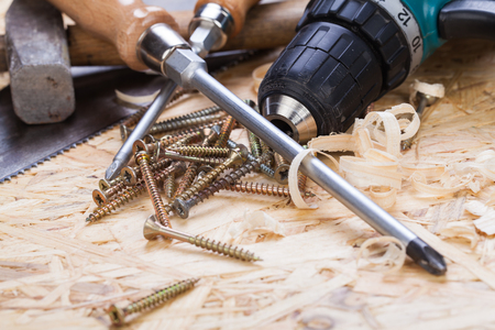 power operated: Battery-operated portable hand drill with timber, screwdrivers and screws surrounded by fresh wood shavings in a carpentry, joinery, DIY or construction concept