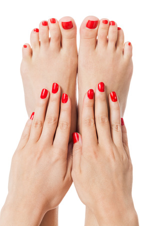bare foot: Woman with beautiful neatly manicured red finger and toenails sitting with bare feet clasping her ankles to display her nails, closeup on white in a fashion and beauty concept