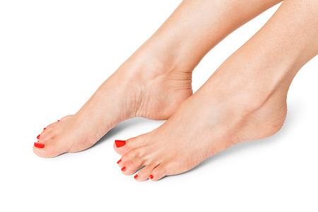Sexy schlanke weibliche Füße mit sorgfältig pedikürten modischen roten Nägeln auf weiß mit copyspace angezeigt in der gekreuzten Position