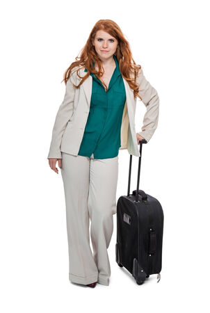Confident business woman walking while carrying luggage photo