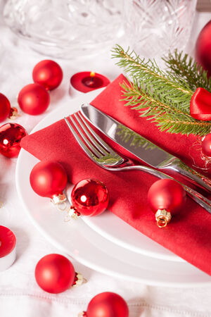 Red themed Christmas place setting with a colorful red napkin on white plates decorated with small red Xmas baubles and burning tea lights for a festive seasonal table photo
