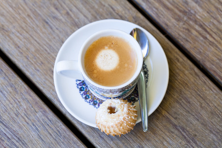 Cup of freshly brewed tea in a floral patterned blue and white cup and saucer with a crunchy biscuit or cookie served on the side