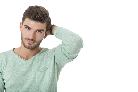 perturbed: Puzzled handsome young man scratching his head with his hand as he looks at the camera with on uncertain perturbed expression, isolated on white