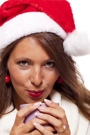 cradling: Cold attractive young woman with a cute smile in a festive red Santa hat sipping a hot mug of coffee did she is cradling in her hands to warm up in the winter weather, on white Stock Photo