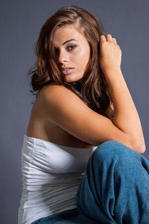 posa sexy: Bello modello femminile che indossa top tubo bianco in posa sexy su sfondo grigio Archivio Fotografico