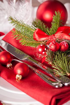 comida de navidad: Red tem�tica lugar configuraci�n de la Navidad con una servilleta de color rojo colorido en las placas blancas decoradas con peque�as bolas de color rojo de Navidad y la quema de velas de t� para una mesa de temporada festiva