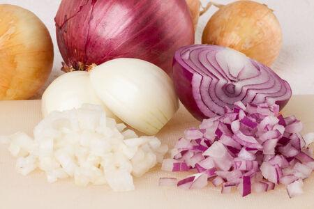 pungent: Intero, sbucciate e tagliate a dadini marrone o cipolla bianca pronta per l'uso come condimento aromatico pungente in cucina su uno sfondo bianco Archivio Fotografico