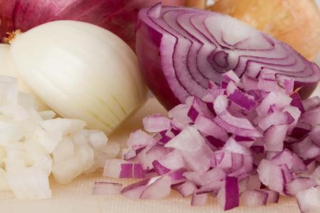 pungent: Tutto, sbucciate e tagliate a dadini marrone o cipolla bianca pronta per essere utilizzato come condimento pungente aromatica in cucina su uno sfondo bianco