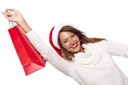 beaming: Happy vivacious Christmas shopper wearing a red Santa hat holding up a colorful red shopping bag with a beautiful beaming smile, isolated on white with copyspace Stock Photo