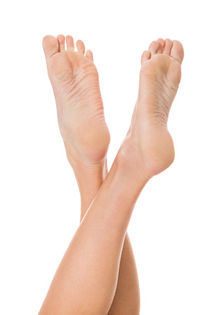 women s feet: Woman with neat manicured natural nails without nail varnish showing her hands and bare feet in a beauty concept on a white