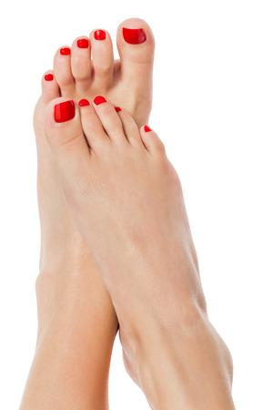 Schlank sexy Frauenfüße mit Sorgfalt vollständig pedicured modischen roten Nägeln im gekreuzten Position auf weiß mit copyspace angezeigt