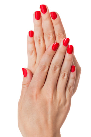 women  s fashion: Woman with beautiful manicured red fingernails gracefully crossing her hands to display them to the viewer on a white in a fashion, glamor and beauty concept