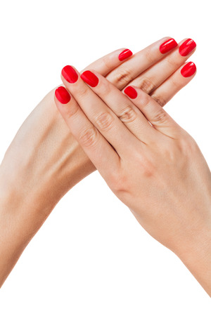 gracefully: Woman with beautiful manicured red fingernails gracefully crossing her hands to display them to the viewer on a white background in a fashion, glamor and beauty concept
