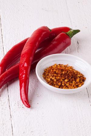 pungent: Fresco rosso e giallo peperoncino con una piccola ciotola di secco spezie pepe di cayenna per l'uso come condimento pungente caldo e aroma in cucina