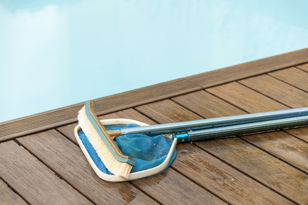 pool deck: Wall Brush and Leaf Skimmer Maintenance Tools on Deck Beside Swimming Pool