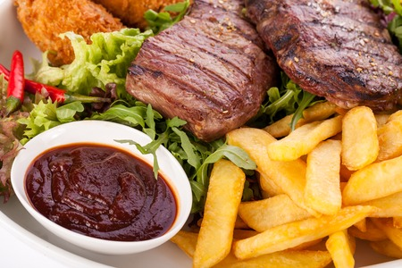 steak beef: Wholesome platter of mixed meats including grilled steak, crispy crumbed chicken and beef on a bed of fresh leafy green mixed salad served with French fries and chutney or BBQ sauce in a dish