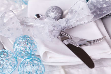 silver cutlery: Stylish blue and silver Christmas table setting with a pretty banner bow on white dinnerware with silver cutlery, pine cones and baubles, high angle close up view