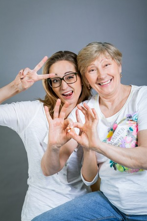 resemblance: Loving grandmother and teenage granddaughter posing for a portrait holding hands and smiling at the camera, on a gray studio
