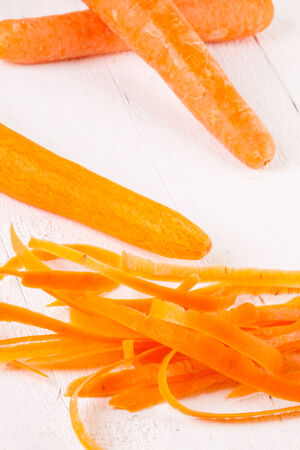cooking implement: Fresh peeled carrots sliced into thin julienne carrot batons for with a metal kitchen cutter on a white