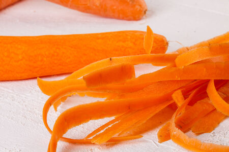 cooking implement: Fresh peeled carrots sliced ??into thin julienne carrot batons for with a metal kitchen cutter on a white background Stock Photo