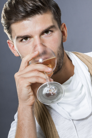 inscrutable: Sexy handsome young man with a beard wearing scarf on elegant drinking white wine and looking at the camera with a serious expression intense