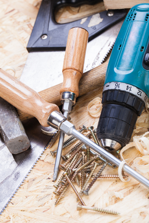 joinery: Battery-operated portable hand drill with timber, screwdrivers and screws surrounded by fresh wood shavings in a carpentry, joinery, DIY or construction concept
