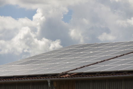 converting: Photovoltaic solar panels on a roof for converting the solar energy of the suns radiant emissions to electricity in a sustainable alternative resource in an eco friendly power and energy concept