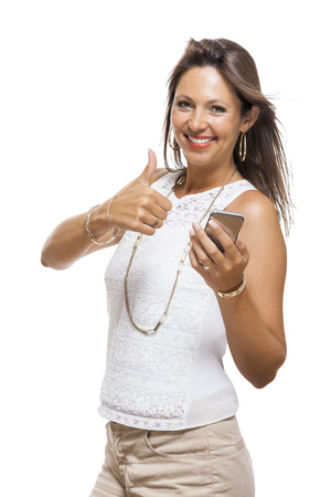 ravishing: Vivacious attractive woman reacting to a text message on her mobile phone flicking her hair in the air and staring at the phone with her mouth open, on white with copyspace Stock Photo