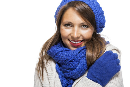 bonnet up: Close up Pretty Smiling Young Woman Wearing Winter Knit Outfit with Blue Bonnet, Scarf and Gloves. Captured in Studio with White Background While Looking at the Camera.