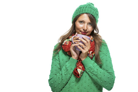 coffeebreak: Close up Pretty Young Woman Wearing Green and Red Winter Fashion, Holding a Cup of Coffee While Smiling at the Camera. Isolated on White Background.