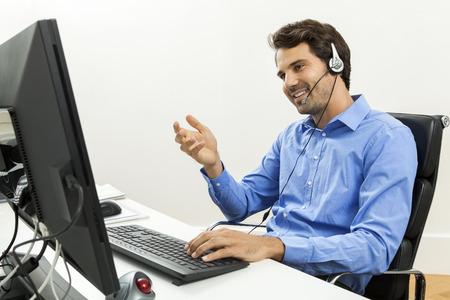 Attraktive unrasiert junger Mann trägt ein Headset mit Online-Chat und Unterstützung auf einem Client-Dienste von Helpdesk, als er Typen in Informationen auf seinem Computer