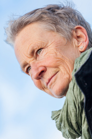 spontaneous expression: happy grey-haired elderly woman senior outdoor portrait smiling