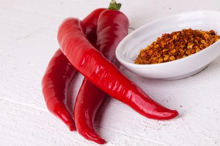 pungent: Fresco rosso e giallo peperoncino con una piccola ciotola di secco spezie pepe di cayenna per l'uso come condimento caldo pungente e aroma in cucina Archivio Fotografico