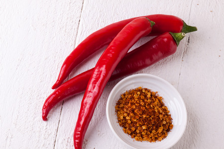 flavorings: Fresh red and yellow chili peppers with a small bowl of dried cayenne pepper spice for use as a pungent hot seasoning and flavoring in cooking Stock Photo