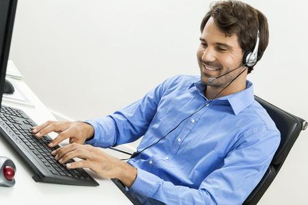 Aantrekkelijke ongeschoren jonge man draagt een headset biedt online chat en ondersteuning op een client services van helpdesk als hij informatie op zijn computer typen Stockfoto