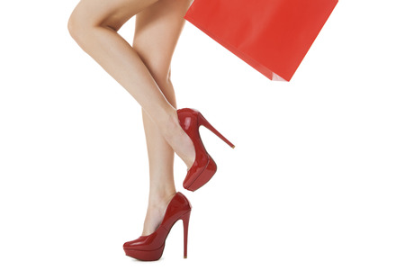 shapely legs: Legs Shot - Woman Legs with Flawless Skin in Red High Heels Shoes Lifting One Leg While Carrying Red Paper Bag. Isolated on White Background.