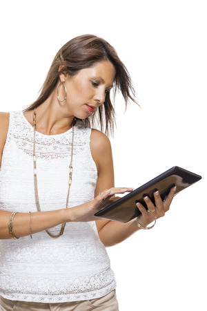 simultaneously: Attractive young business woman standing chatting on a mobile while simultaneously reading a tablet computer with a smile, isolated on white