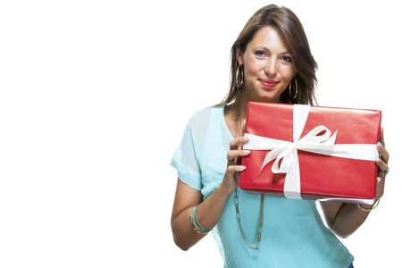 giftwrapped: Close up Portrait of Happy Young Woman in Casual Clothing Holding a Red Big Gift Box with White Ribbon While Looking at the Camera. Isolated on White Background.