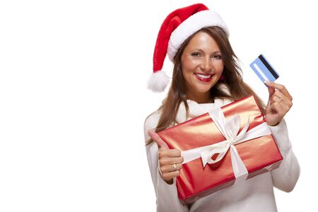 giftwrapped: Smiling woman wearing a red Santa hat purchasing Christmas gifts on a bank card holding up a colorful red giftwrapped box with a happy smile and a thumbs up gesture of success, isolated on white