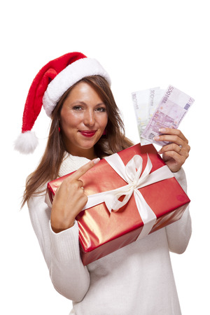 giftwrapped: Vivacious beautiful young woman wearing a Santa hat with a large red Christmas gift and money, conceptual of successful Xmas shopping and payment, on white Stock Photo