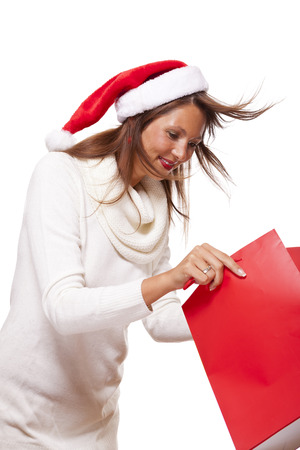 vivacious: Happy vivacious Christmas shopper wearing a red Santa hat holding up a colorful red shopping bag with a beautiful beaming smile, isolated on white with copyspace Stock Photo