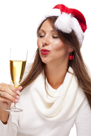 mischievous: Playful woman wearing a festive red Santa hat and holding a flute of champagne celebrating Christmas blowing a kiss across the palm of her hand with a mischievous smile, on white Stock Photo