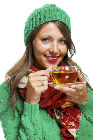 pout: Attractive young woman in a trendy green knitted winter ensemble warming up with a cup of hot tea isolated on white