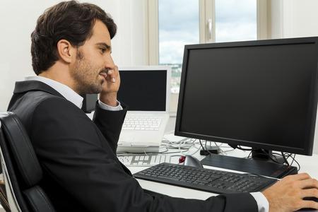 monitor de computadora: Hombre de negocios con estilo en un juego que se sienta en su escritorio en la oficina de hablar por teléfono con el fin de su monitor de la computadora en blanco